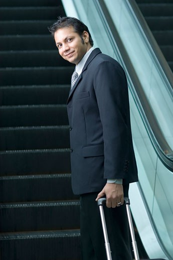 Portrait of a businessman standing in front of an escalator : Stock Photo