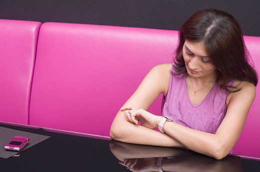 Young woman looking at her wristwatch : Stock Photo