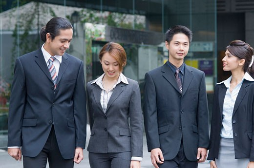 Two businessmen walking with two businesswomen, Singapore : Stock Photo