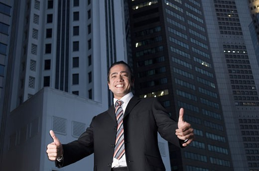 Portrait of a businessman making thumbs up signs and smiling, Singapore : Stock Photo