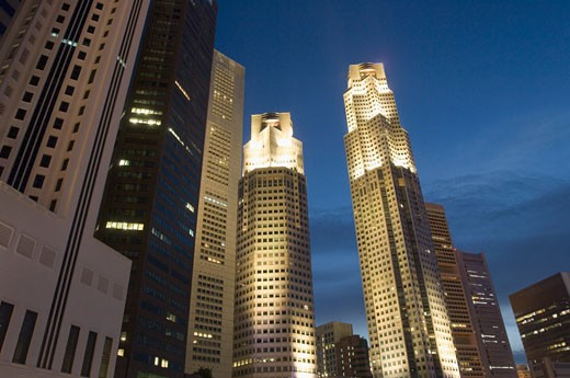 Low angle view of skyscrapers lit up at dusk, Singapore : Stock Photo