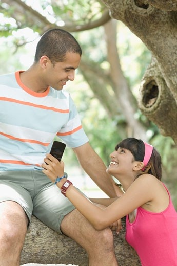Side profile of a young woman holding a mobile phone and looking at a young man sitting on a tree branch  : Stock Photo