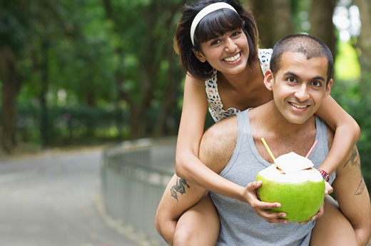 Portrait of a young woman riding piggyback on a young man and holding a coconut : Stock Photo