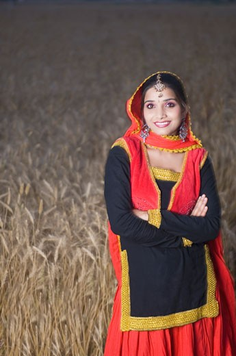 Portrait of a young woman standing in a wheat field and smiling : Stock Photo