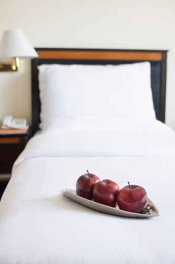 Three apples in a plate on the bed in a hotel room : Stock Photo