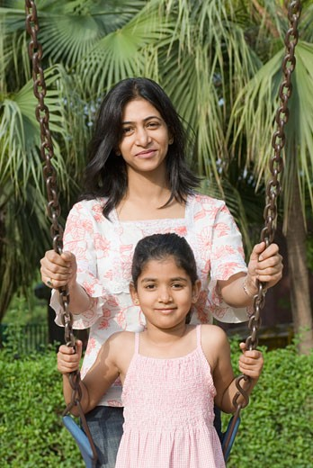 Portrait of a girl on a swing with her mother standing beside her : Stock Photo