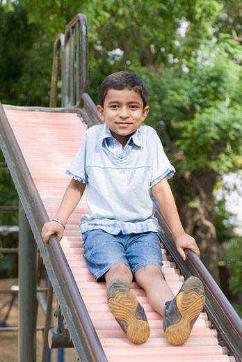 Portrait of a boy sliding on a slide : Stock Photo