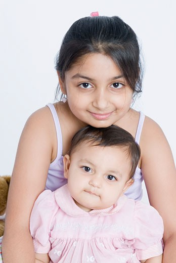 Portrait of a girl sitting with her sister : Stock Photo
