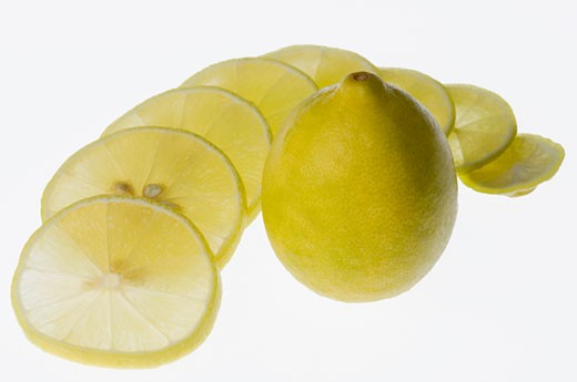 Close-up of a lemon with lemon slices : Stock Photo