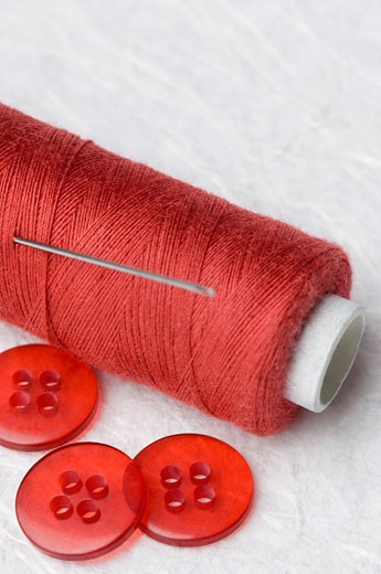 Close-up of red buttons and a needle with a spool of red thread : Stock Photo