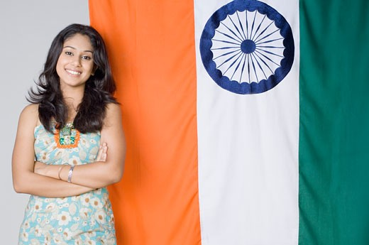 Portrait of a young woman standing with her arms crossed in front of an Indian flag : Stock Photo