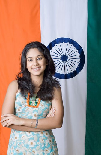 Stock Photo: 1657R-17495 Portrait of a young woman standing with her arms crossed in front of an Indian flag