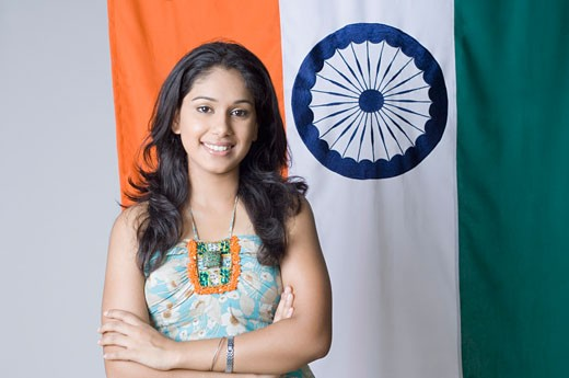 Stock Photo: 1657R-17496 Portrait of a young woman standing with her arms crossed in front of an Indian flag
