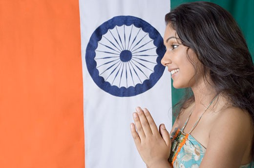 Side profile of a young woman smiling in front of an Indian flag : Stock Photo