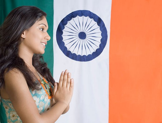 Side profile of a young woman standing in front of an Indian flag : Stock Photo