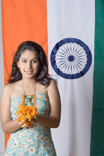 Portrait of a young woman standing in front of an Indian flag : Stock Photo