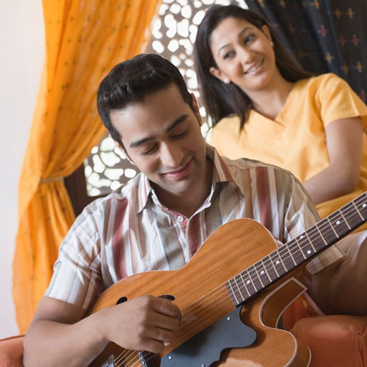 Young man playing a guitar with a young woman sitting behind him : Stock Photo