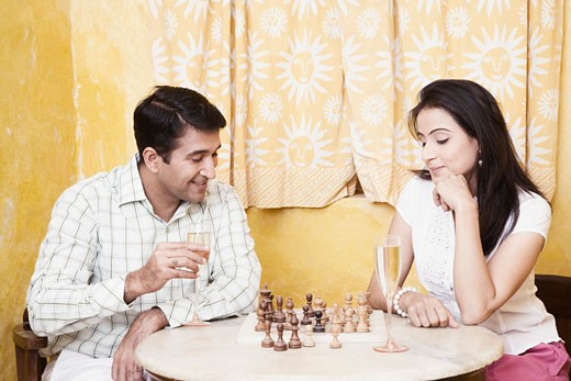 Mid adult couple playing chess at a table : Stock Photo
