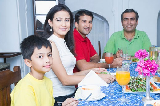 Portrait of a mid adult couple sitting with their son and a mid adult man at a dining table : Stock Photo