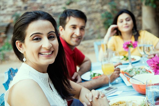 Stock Photo: 1657R-18364 Mid adult woman sitting with her friends at a dining table