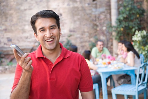 Portrait of a mid adult man holding a mobile phone and smiling with his friends sitting in the background : Stock Photo