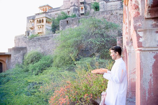 Stock Photo: 1657R-18565 Side profile of a young man holding a plate of powder paint and standing at the balcony of a fort, Neemrana Fort Palace, Neemrana, Alwar, Rajasthan, India
