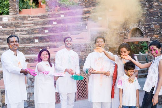 Two mid adult couples and a young couple with a boy celebrating holi : Stock Photo