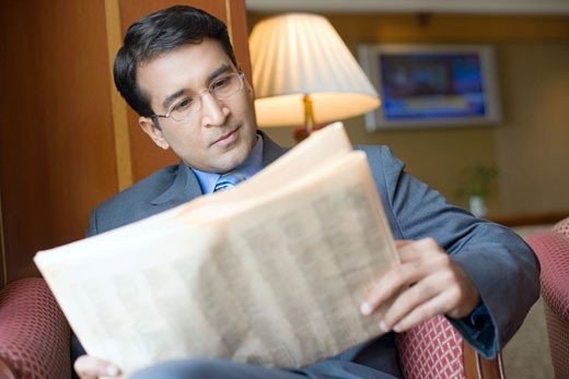 Close-up of a businessman sitting in an armchair and reading a newspaper : Stock Photo