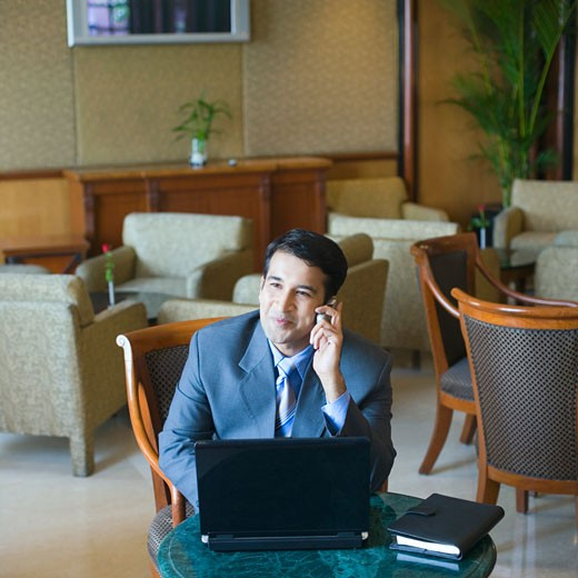 Stock Photo: 1657R-18673 Businessman sitting in front of a laptop and talking on a mobile phone in a lobby