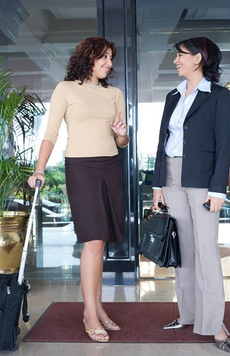 Two businesswomen standing near a door and talking to each other : Stock Photo