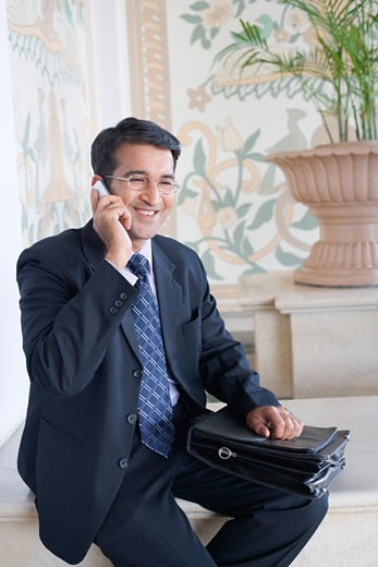 Stock Photo: 1657R-18830 Businessman talking on a mobile phone and smiling