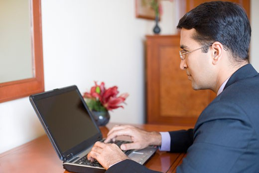 Side profile of a businessman working on a laptop : Stock Photo