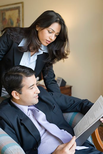 Businessman with his assistant reading a file : Stock Photo