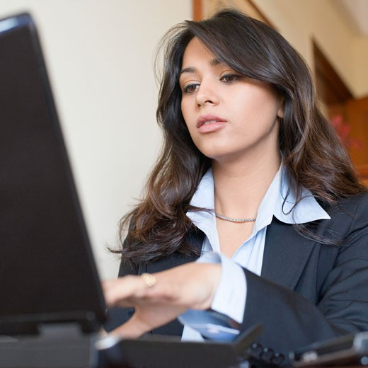 Businesswoman using a computer in an office : Stock Photo