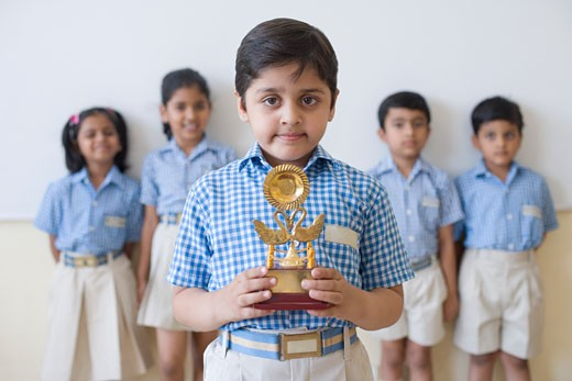 Portrait of a schoolboy holding a trophy with his classmates in the background : Stock Photo