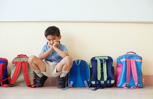 Portrait of a schoolboy crouching near schoolbags and looking sad : Stock Photo
