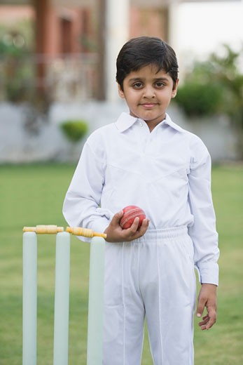 Stock Photo: 1657R-19215 Portrait of a boy holding a cricket ball and smiling