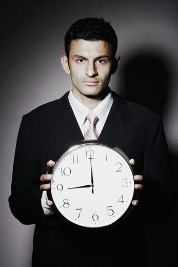 Stock Photo: 1657R-1922 Portrait of a businessman holding a clock