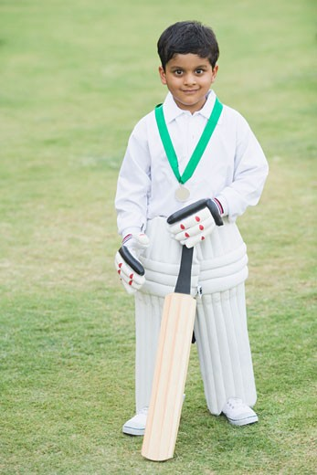 Cricketer standing in a cricket field : Stock Photo