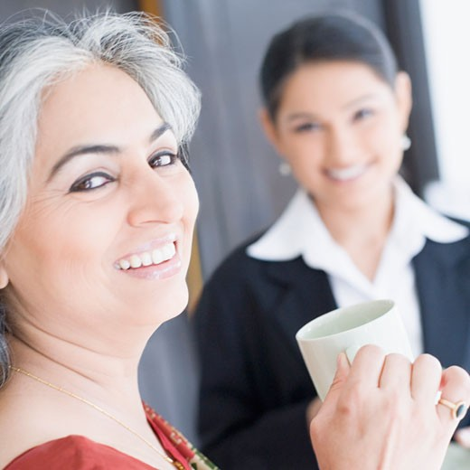 Portrait of two businesswomen holding cups of tea and smiling : Stock Photo