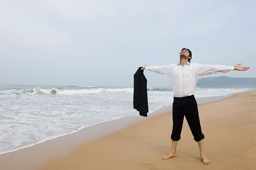 Businessman standing on the beach with his arms outstretched : Stock Photo
