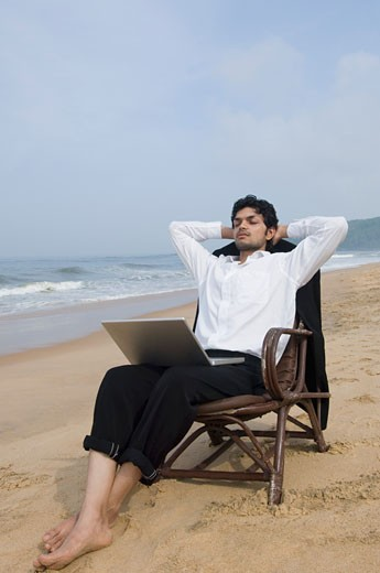 Businessman sitting in an armchair with a laptop on the beach : Stock Photo