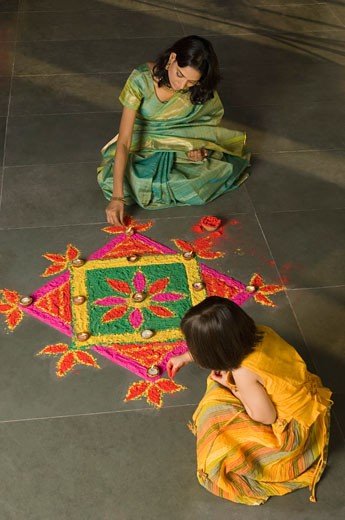 High angle view of a young woman making rangoli with her daughter : Stock Photo