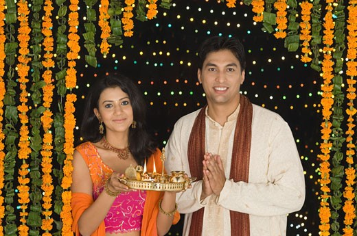 Stock Photo: 1657R-20479 Portrait of a young woman holding a diwali thali with a young man standing beside her