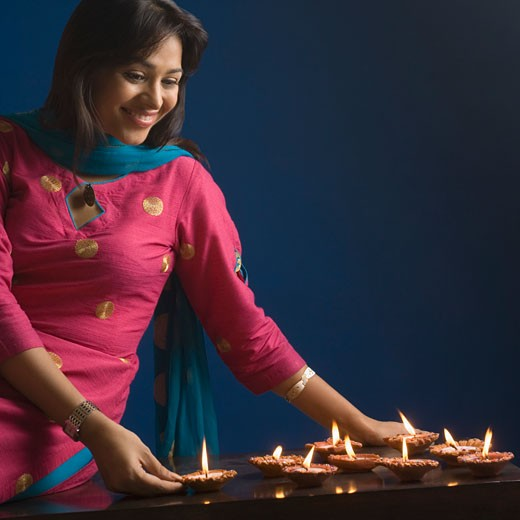 Stock Photo: 1657R-20593 Close-up of a young woman looking at oil lamps and smiling