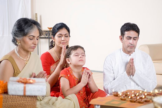 Family praying in front of figurines of God : Stock Photo