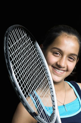 Portrait of a teenage girl with a badminton racket and smiling : Stock Photo
