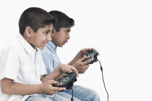 Side profile of two boys playing video game : Stock Photo
