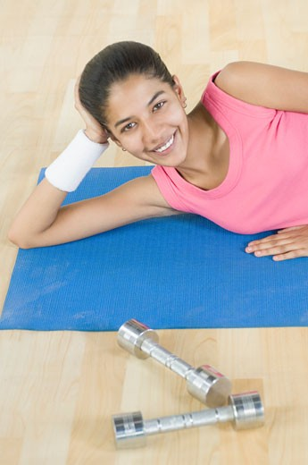High angle view of a young woman lying on an exercise mat and smiling : Stock Photo