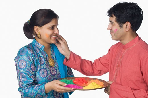Side profile of a mid adult man applying powder paint on a mid adult woman's face : Stock Photo